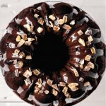 Overhead image of a chocolate bundt cake with a shiny chocolate glaze and candied ginger with text overlay