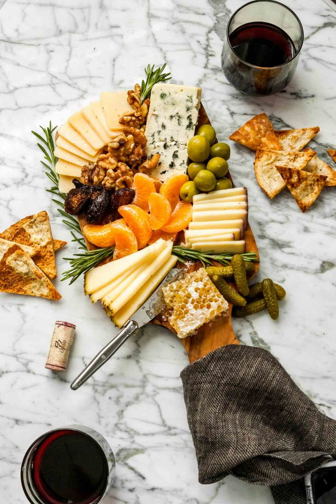 overhead image of a wood cutting board piled high with cheese, olives, clementines, rosemary and honeycomb