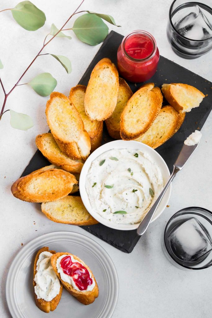overhead image of a slate board topped with a bowl of whipped ricotta and toasted crostini. A plate with mini toasts topped with ricotta and curd off to the side