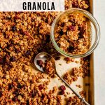 Overhead image of granola on a baking sheet with a spoon laid over top and a jar off to the side with granola in it