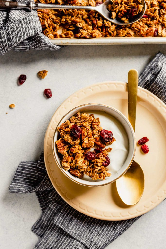 Overhead image of a white bowl filled with yogurt and granola on a cream colored plate with a baking sheet of granola in the background.