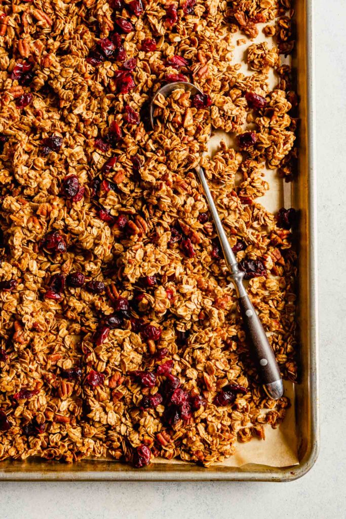 Overhead image of granola on a baking sheet with a spoon laid over top