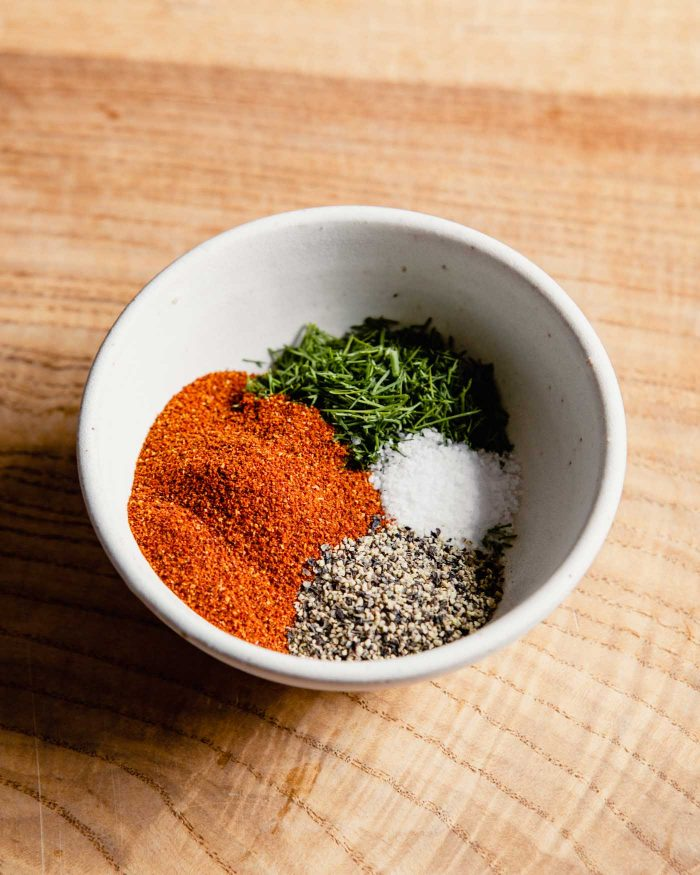 a small white bowl filled with paprika, salt, pepper and fresh dill