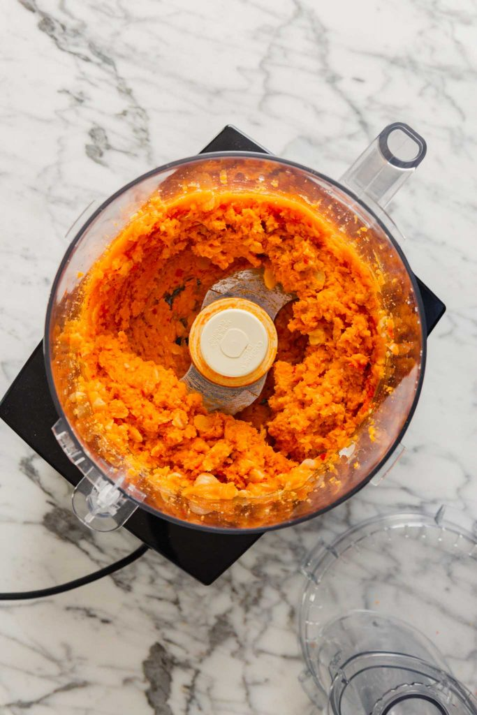 Overhead image of chopped chickpeas and sweet potato puree in a food processor