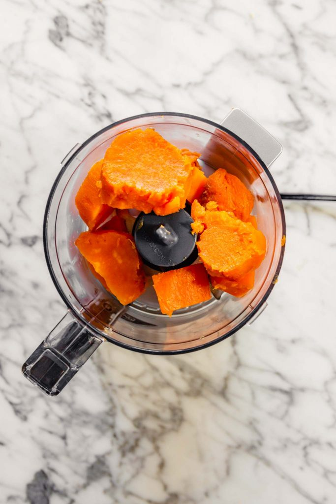 Overhead image of peeled roasted sweet potatoes in a mini food processor set on a white marble table