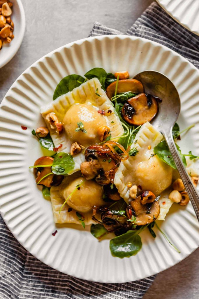 Close up overhead image of ravioli in a cream bowl with watercress, nuts and thyme. A spoon in the bowl.