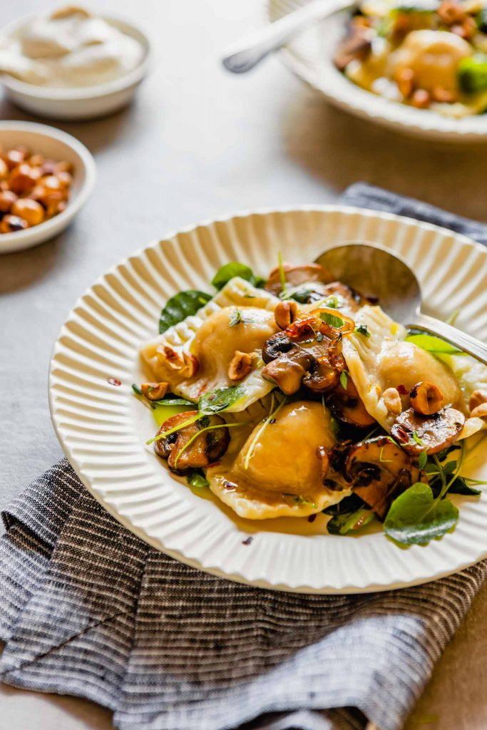 side angle of vegan ravioli with mushrooms, watercress and hazelnuts in a white bowl set on a marble table.