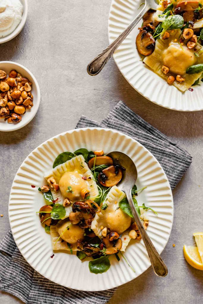 Overhead image of ravioli in a cream bowl with watercress, nuts and thyme. A spoon in the bowl with nuts in a bowl off to the side