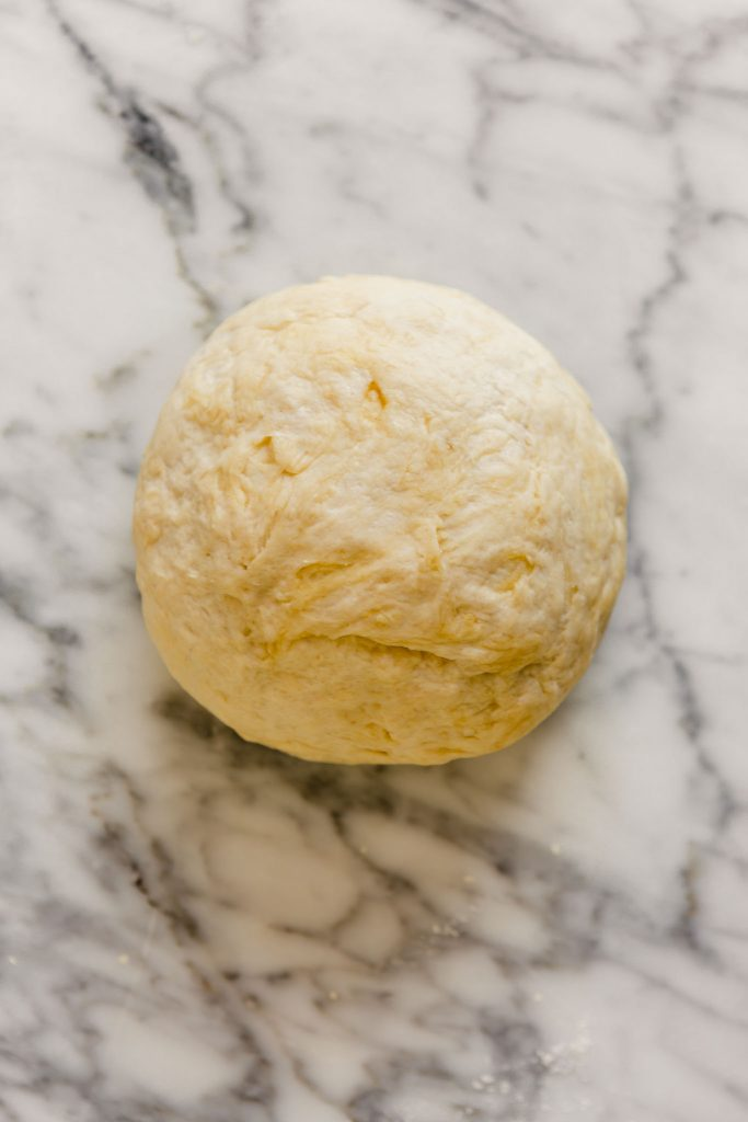 overhead image of a large dough ball on a marble table