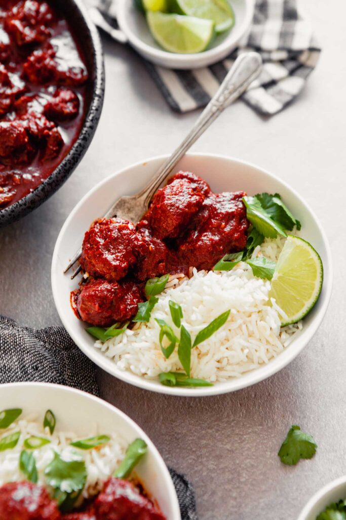 Side angle of deep red pieces of pork arranges in a white bowl over rice with herbs and a lime wedge set on a gray table