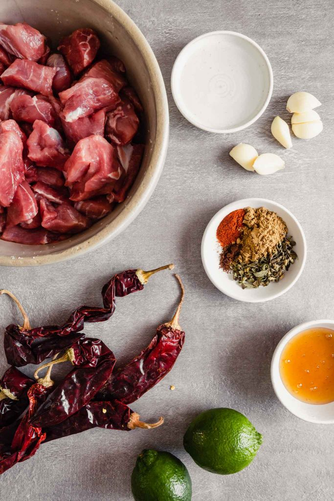 Overhead image of spices, dried chiles, pork, garlic and vinegar arranged on a gray table.
