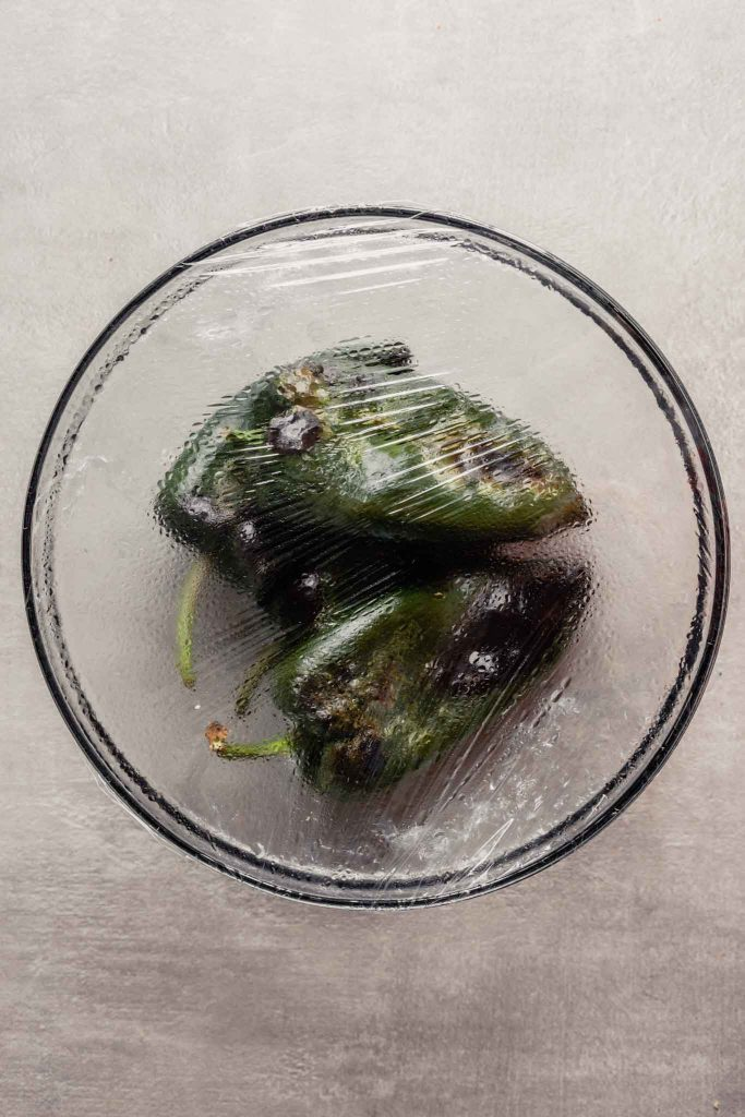 oberhead image of roasted poblano peppers in a bowl covered with plastic wrap