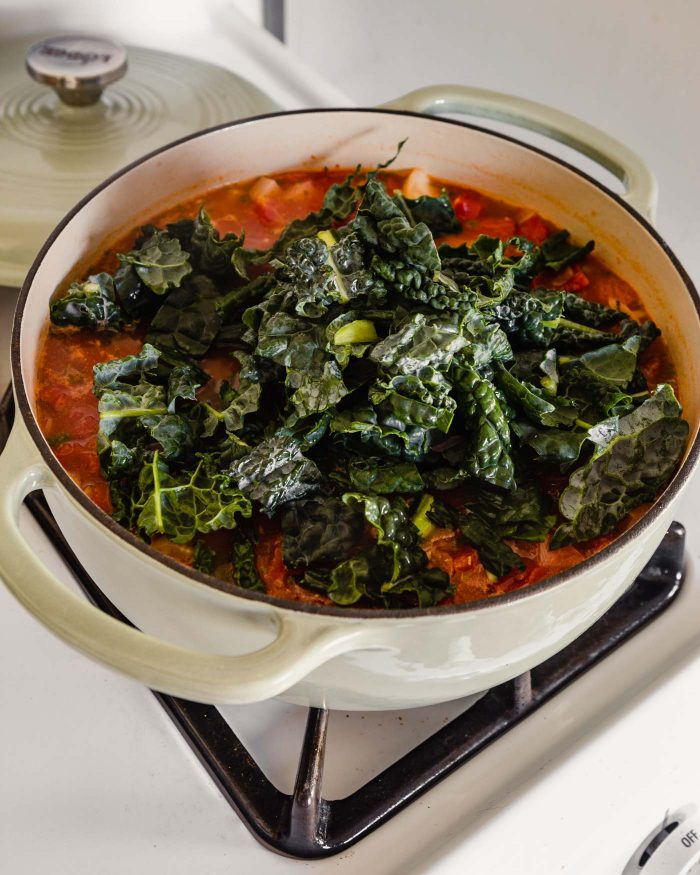 Heaping kale on top of a tomato soup mixture in a large Dutch oven on stove top