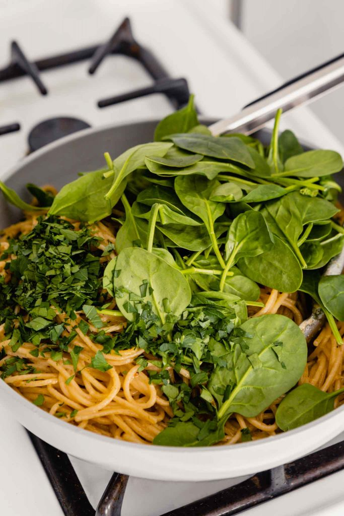 image of spinach and parsley on top of a bed of noodles in a gray skillet on the stove