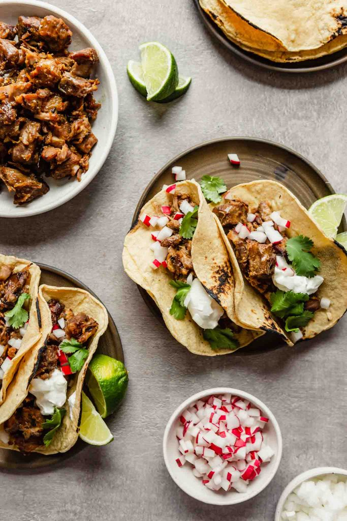 Overhead image of yellow corn tortillas filled with pork and topped with radish, onion, and cilantro set on brown plates with lime wedges.