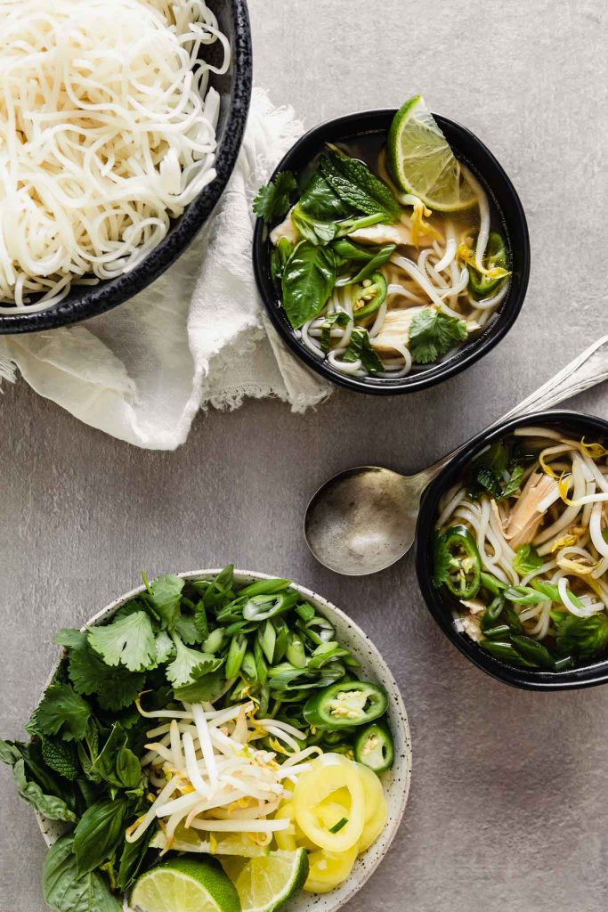 Overhead image of bowls of pho soup in a black bowl set on a gray table