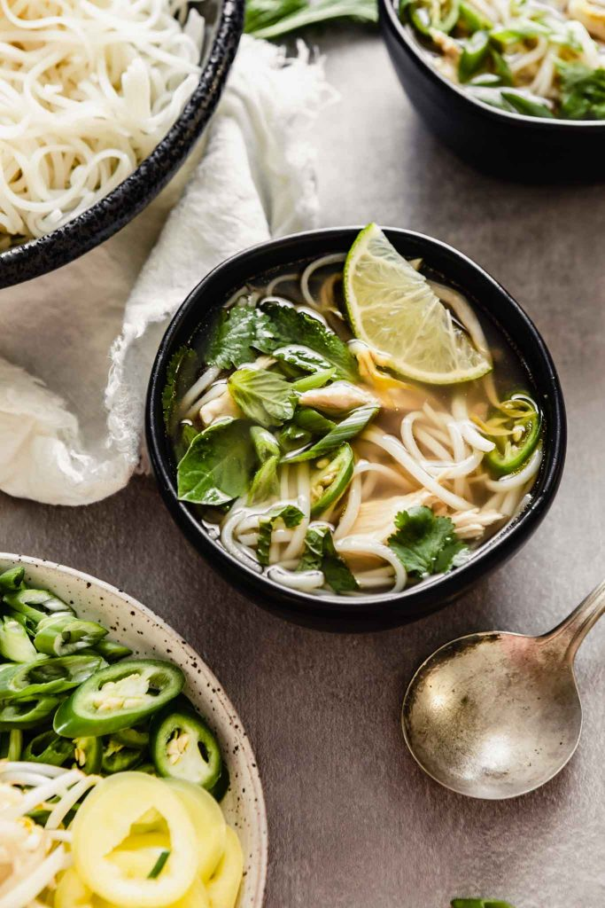 Overhead image of pho soup in a black bowl set on a gray table