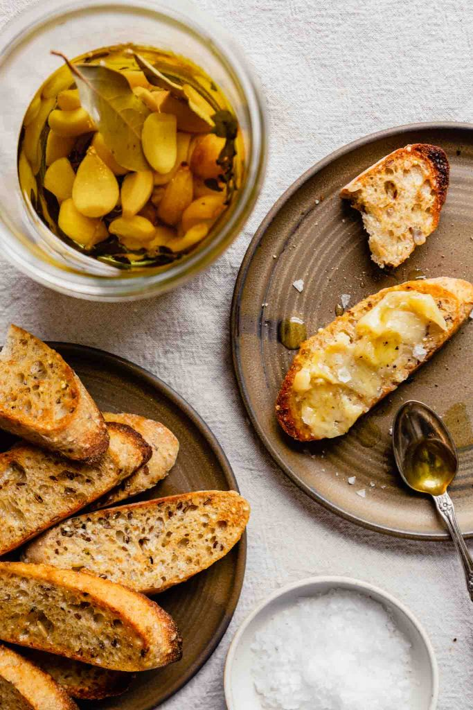 overhead image of a brown plate with a toasted piece of bread with garlic spread over it. A jar of garlic cloves and oil off to the side