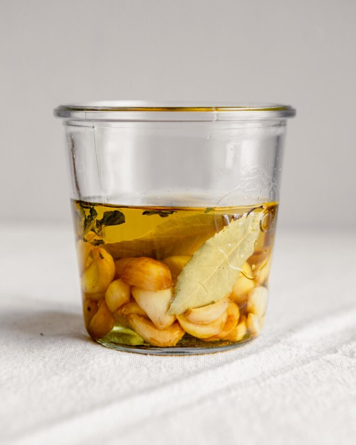 Side angle of garlic cloves and bay leaves in a jar covered with oil