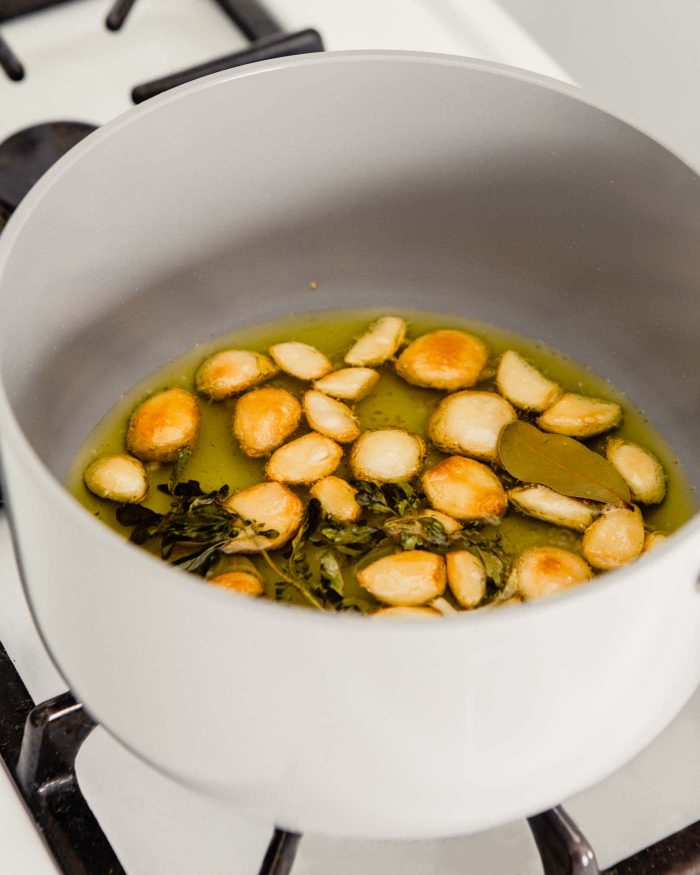 photo of lightly golden brown garlic cloves in a saucepan with oil and herbs