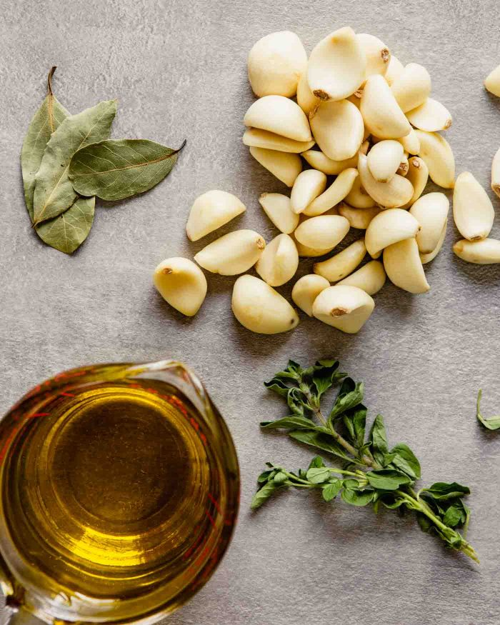 Overhead image of garlic cloves, bay leaves, oregano sprigs and olive oil set out on a gray table