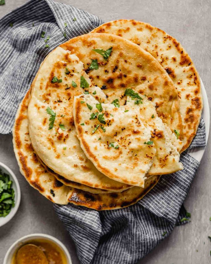 Homemade naan bread stacked on a blue napkin on a white plate sprinkled with parsley
