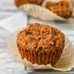 Bran muffins set on a wire rack on top of a marble table