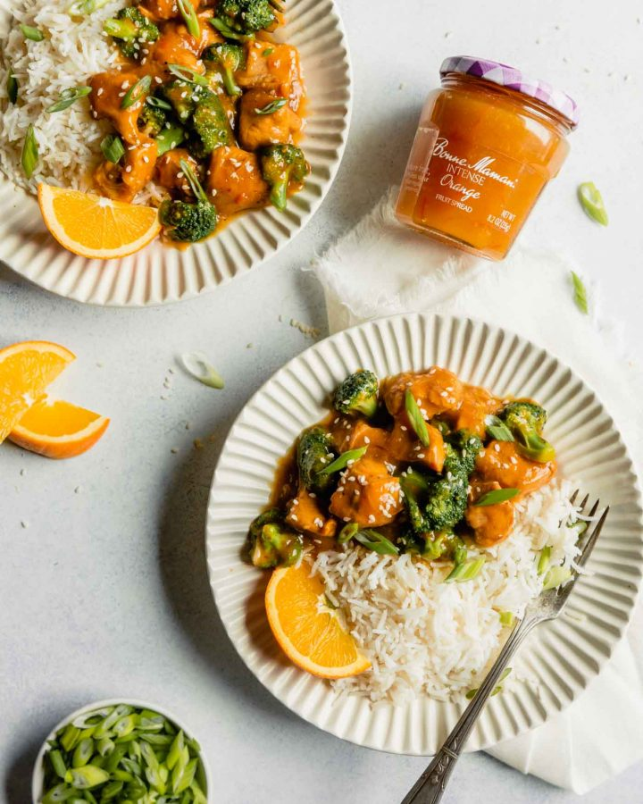 Overhead image of two white plates with orange chicken, broccoli and rice arranged on top with chopped green onions off to the side.