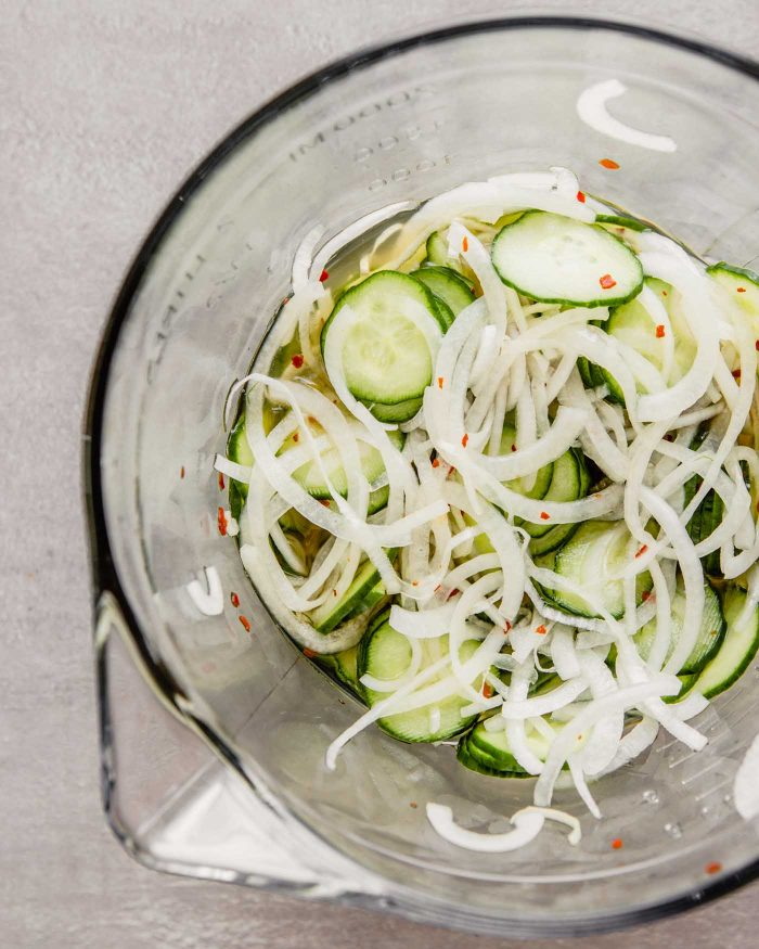 overhead image of thinly sliced cucumbers and onions in a glass bowl with a pickling liquid and red pepper flakes