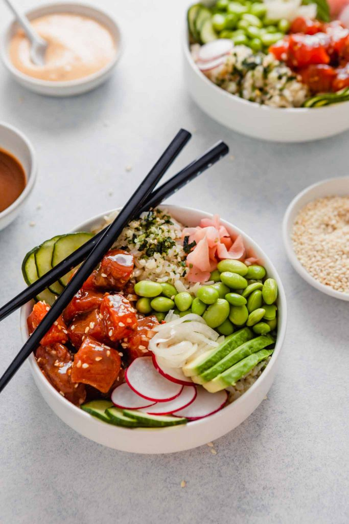 Side angle of a bowl filled with raw salmon, edamame, cucumbers, ginger and avocado set on a blue table with bowls of sauce and chopsticks