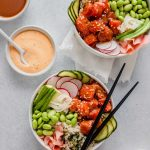 Overhead image of two bowsl filled with raw salmon, edamame, cucumbers, ginger and avocado set on a blue table with bowls of sauce and chopsticks