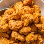 Close up overhead image of breaded and baked cauliflower bites in a white bowl set on a dark napkin