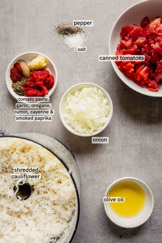 overhead image of ingredients (cauliflower, oil, onion, tomatoes, tomato paste, spices) laid out on a gray counter