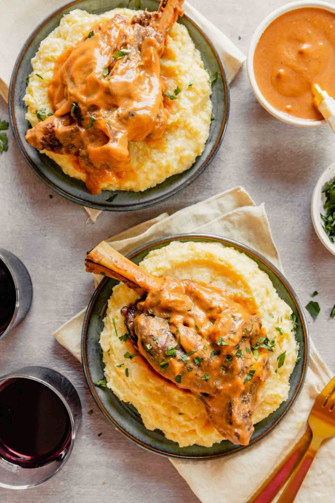 Overhead image of lamb shanks covered with sauce set over a bed of polenta on blue plates