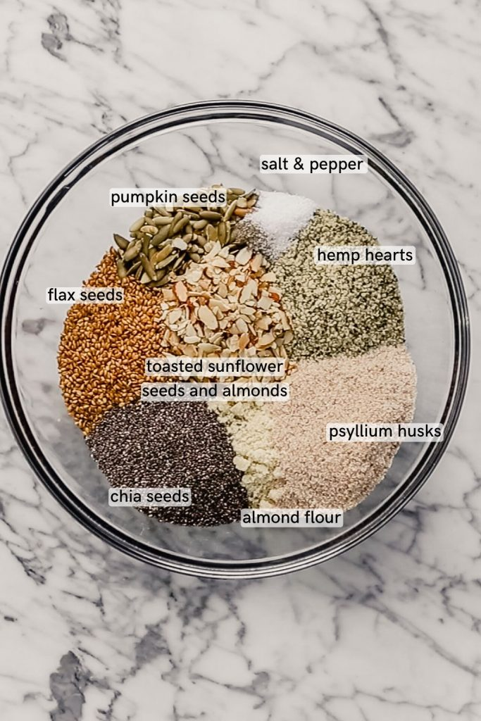 Overhead image of nuts and seeds in a glass bowl set on a marble table