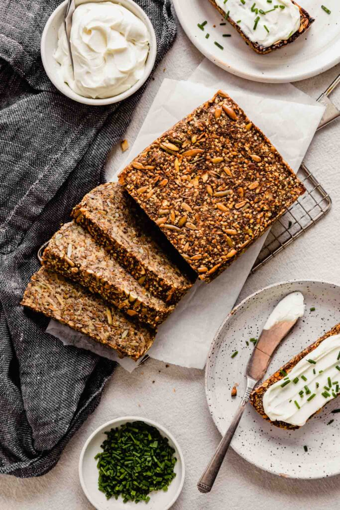 Overhead image of nut and seed bread set on a table with plates of bread slices topped with cream cheese and chives