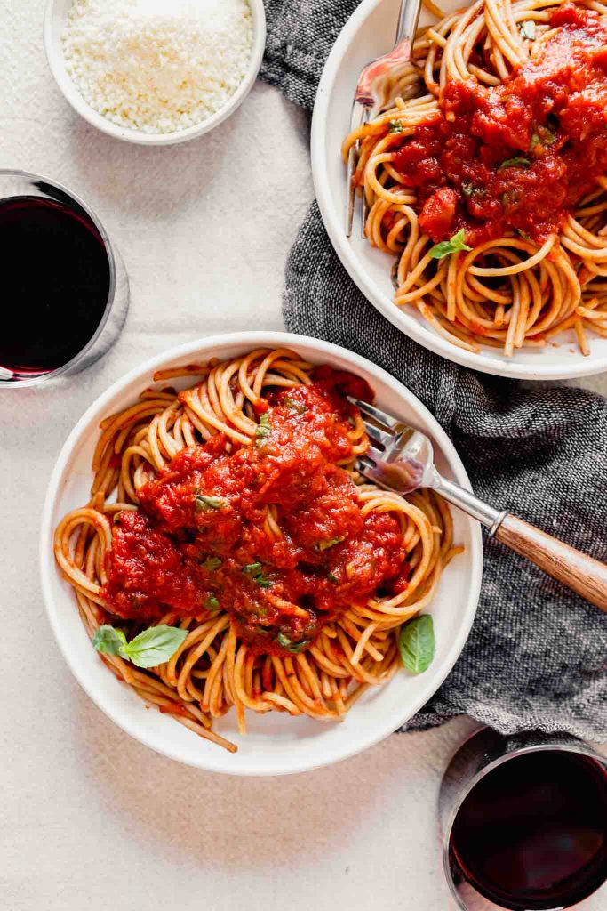 overhead image of spaghetti and red sauce in a white bowl set on a table with wine and parmesan