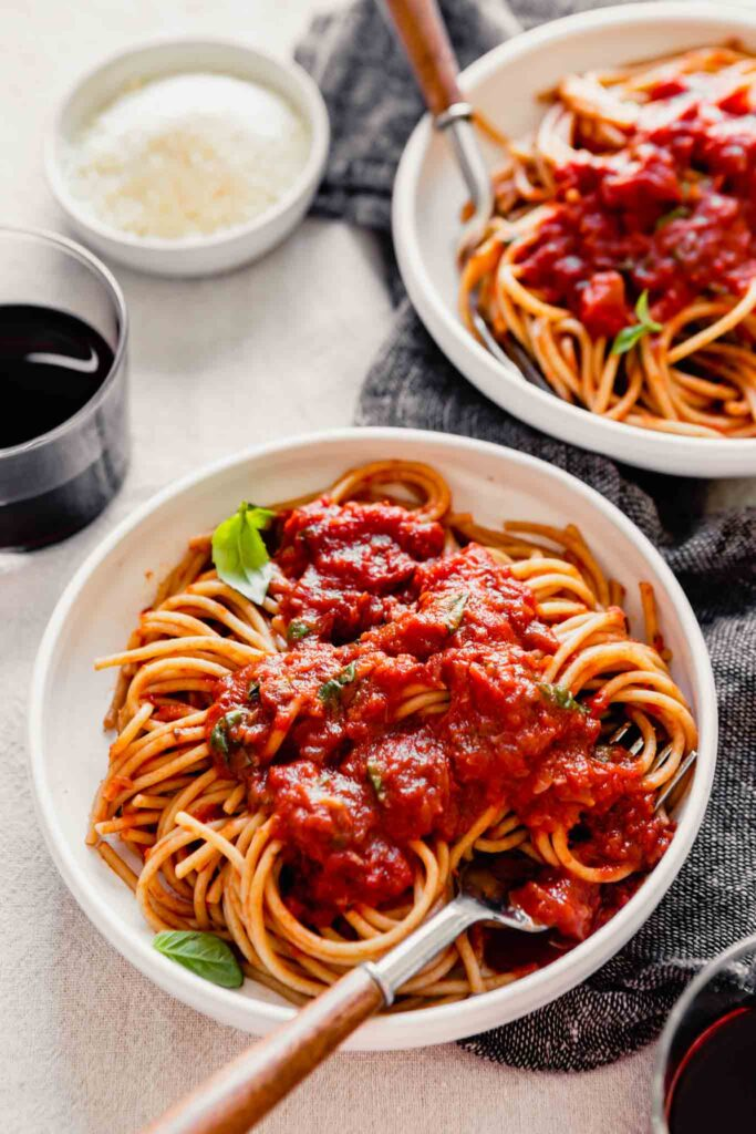 side angle of spaghetti and red sauce in a white bowl on a table with wine and cheese