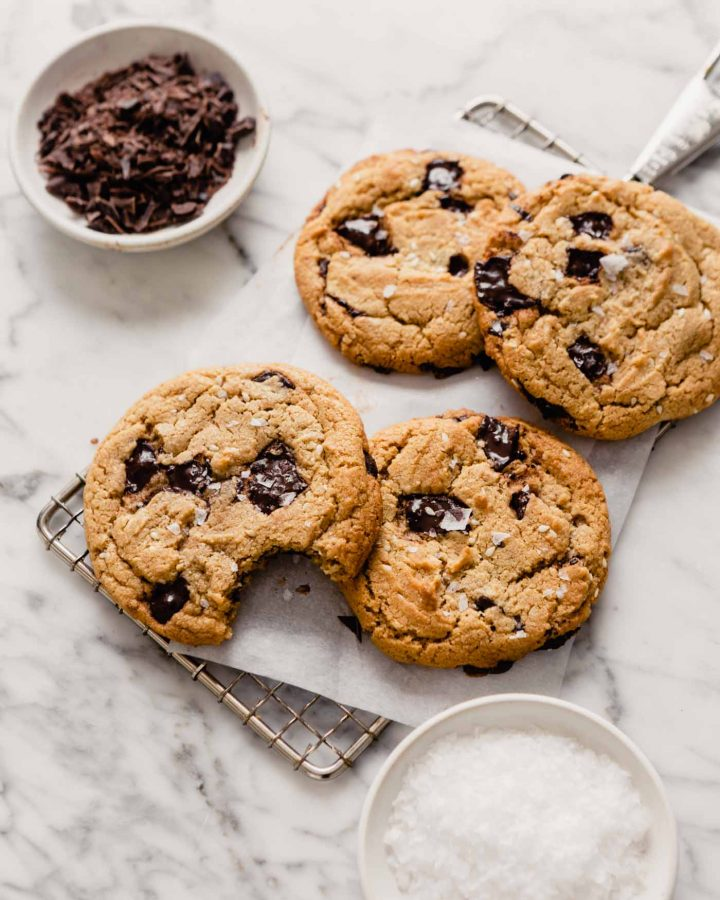 Overhead image of chocolate chip cookies stacked on a cooling rack on top of a marble table with bowls of salt and chocolate set around