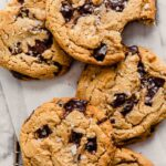 Overhead image of chocolate chip cookies stacked on a cooling rack on top of a marble table.