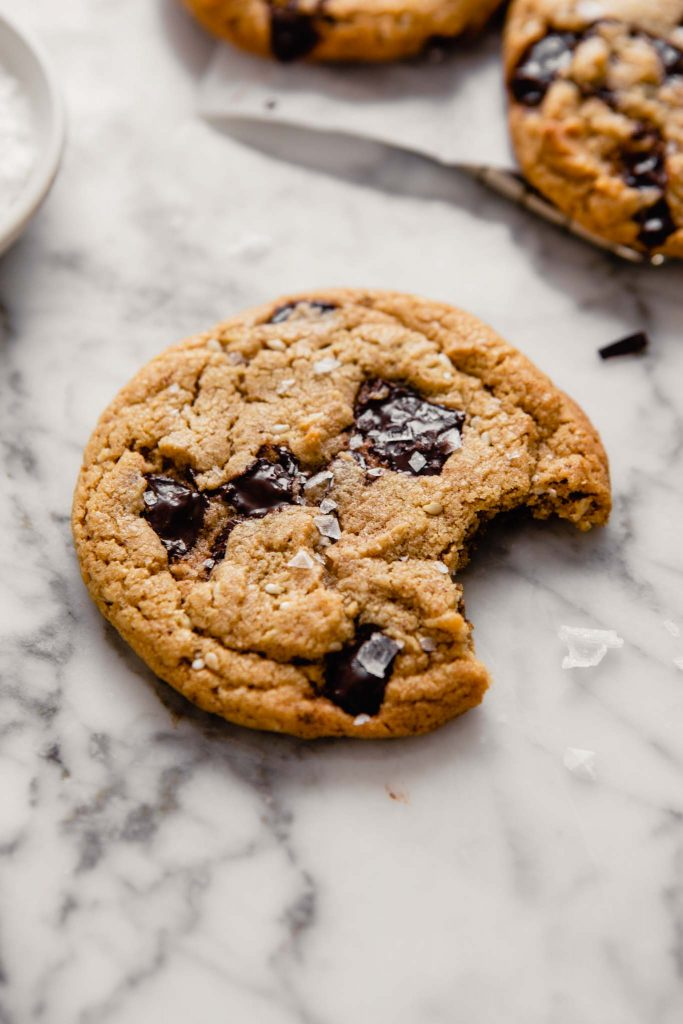 Side angle of a chocolate chip cookie with a bite taken out of it set on a marble table with cookies in the background