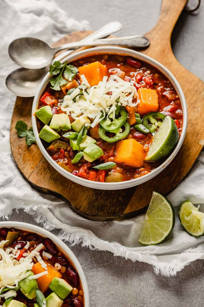 image of chili in two white bowls, one set on a wood board, the other on the counter.