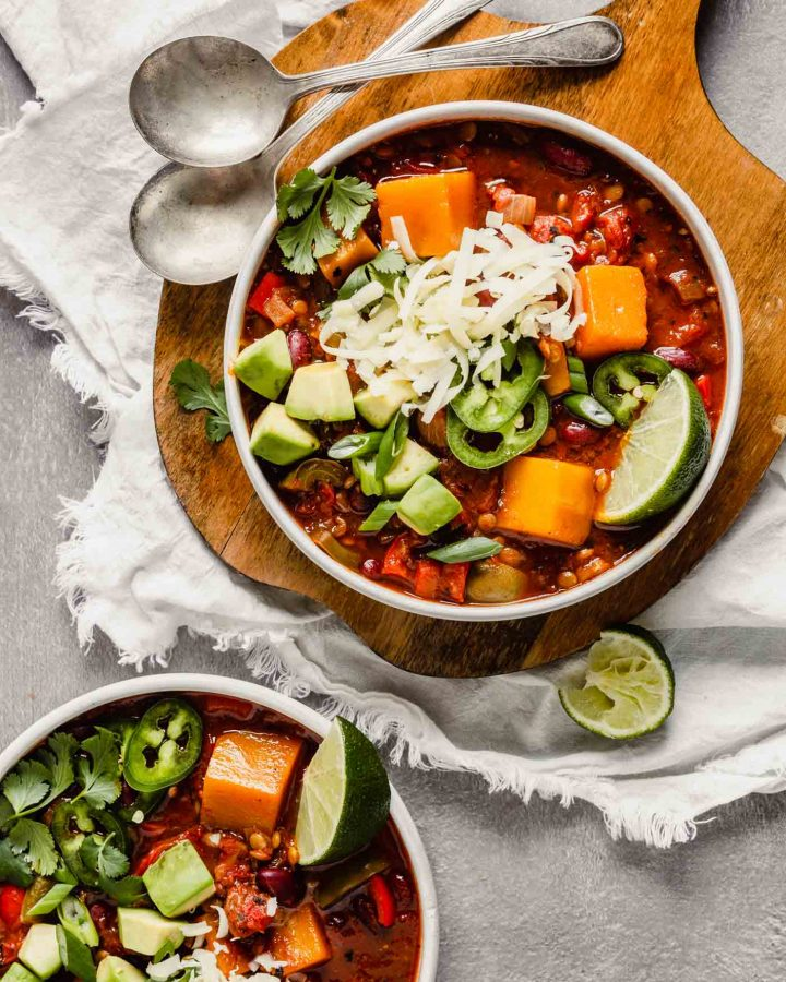 Overhead image of chili in two white bowls, one set on a wood board, the other on the counter. Chili bowls topped with avocado, cilantro, jalapenos, cheese. Lime wedges scattered around.