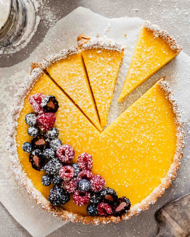 Overhead image of a lemon tart set on parchment paper with powdered sugar and berries scattered around it