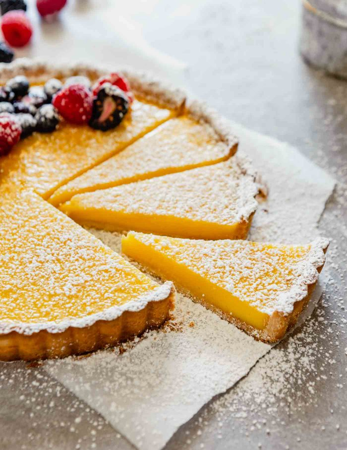 side angle of a slice of lemon tart pulled away from the rest of the tart