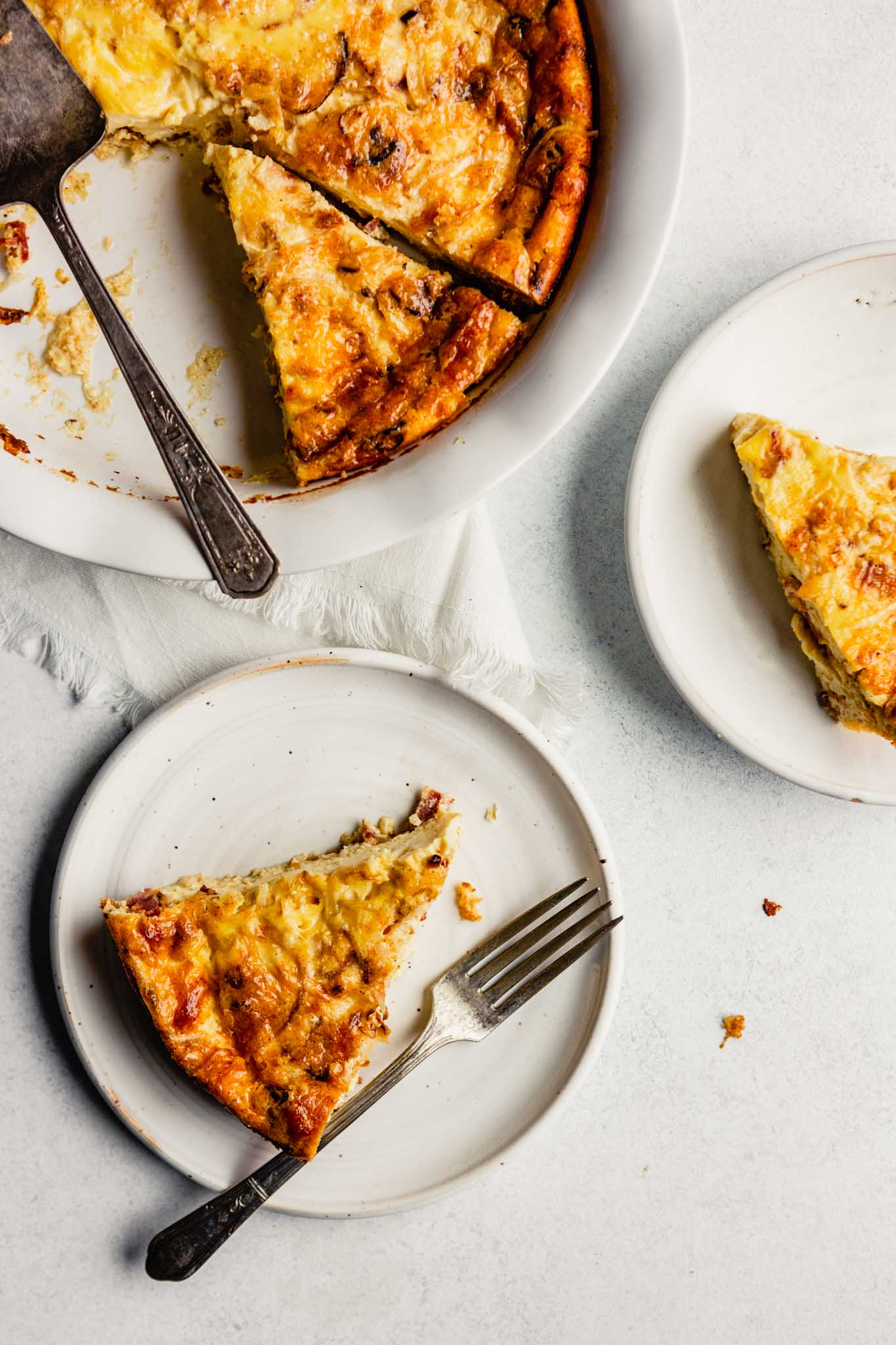 Overhead image of a crustless quiche in a white pie plate set on a white table with plates and pieces set around the quiche..
