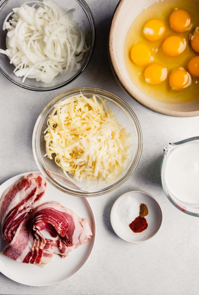 Overhead image of eggs, cheese, onion, bacon, milk and spices prepped and set on a table