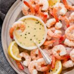 Overhead image of a metal plate filled with ice, shrimp, and a butter sauce in a white bowl