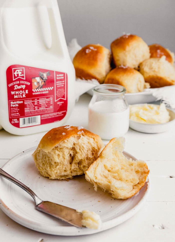 Side angle of a milk roll set on a plate with milk set in the background