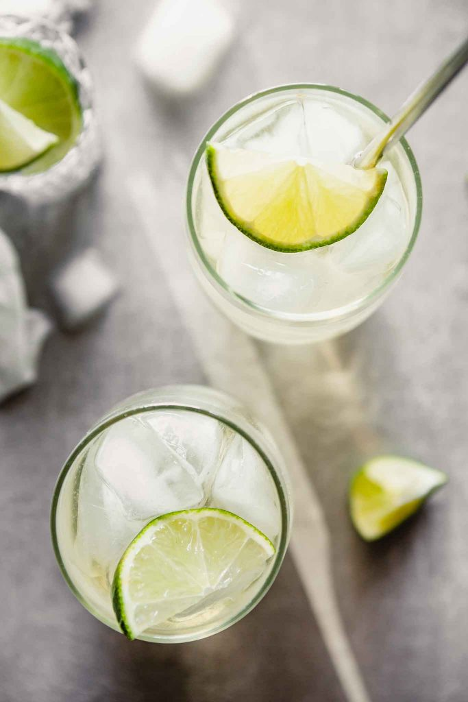 overhead image of high ball glasses filled with a cocktail and a lime wedge.